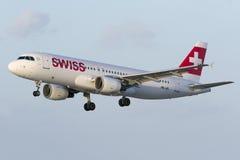 Zwitsers lijnvliegtuig in het vlagerige wind landen Royalty-vrije Stock Foto's