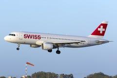 Zwitsers lijnvliegtuig in het vlagerige wind landen Royalty-vrije Stock Afbeeldingen