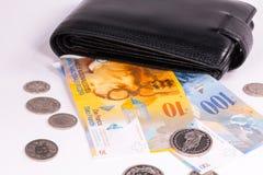 Zwitserse bankbiljetten en muntstukken in een portefeuille op een wit stock foto's