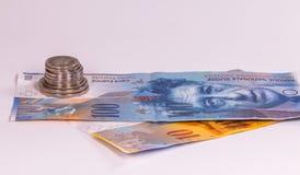 Zwitserse bankbiljetten en muntstukken op een witte achtergrond stock afbeeldingen