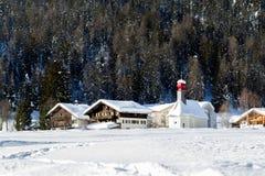 Zwitserse het dorpshuizen van Alpen en een kleine kerk met een rode koepel i royalty-vrije stock foto