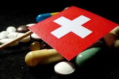 Zwitserse vlag met partij van medische die pillen op zwarte wordt geïsoleerd Stock Foto