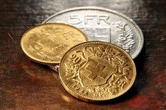 Zwitserse zilveren en gouden muntstukken Stock Foto's