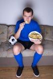 Zwolennika dopatrywania futbol na tv i łasowanie układach scalonych w domu Fotografia Stock