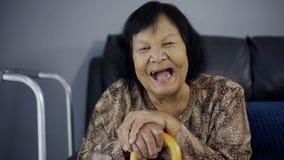Zwolnione tempo śmia się drewnianej trzciny i trzyma starsza kobieta zbiory wideo