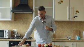 Zwolnione tempo atrakcyjny młody śmieszny mężczyzna taniec, śpiew z kopyścią i podczas gdy gotujący w kuchni w domu zbiory wideo