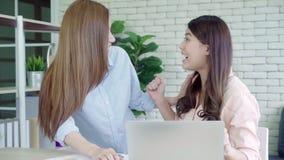 Zwolnione tempo - Azjatyckie biznesowe kobiety czuje szczęśliwe ręki podnoszącą odświętność po słuchają sukcesu Operacyjnego rezu zbiory