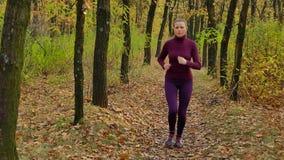 Zwolnione tempo bieg - kobieta biegacz jogging na jesieni lasowej ścieżce Dysponowanego żeńskiego sport sprawności fizycznej mode zbiory