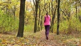 Zwolnione tempo bieg - kobieta biegacz jogging na jesieni lasowej ścieżce Dysponowanego żeńskiego sport sprawności fizycznej mode zdjęcie wideo