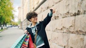 Zwolnione tempo bierze selfie z kolorowymi torba na zakupy stoi outdoors z włosami kobieta, trzyma smartphone i zdjęcie wideo