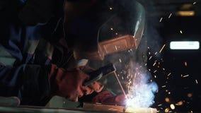 Zwolnione tempo, bocznego widoku spawacz w spaw masce spawa dwa metal części Robociarz w coveralls pracuje indoors zdjęcie wideo