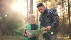 Zwolnione tempo chłopiec mienia mapy pozycja w lesie podczas gdy jego ojciec jest opowiadający i gestykulujący uczący jego syna zbiory wideo