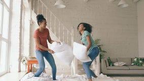 Zwolnione tempo dwa mieszającej biegowej młodej ładnej dziewczyny skacze na łóżka i walki poduszkach ma zabawę w domu zdjęcie wideo