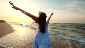 ZWOLNIONE TEMPO: Dziewczyna bieg w płytkiej wodzie przy zmierzchem Dziewczyna w białej sukni biega przy wodną ` s krawędzią blisk zbiory wideo