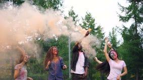 Zwolnione tempo dziewczyny i faceci tanczy i skacze z dymnymi racami przy plenerowym przyjęciem, skórą i ubraniami, zakrywa z zbiory wideo