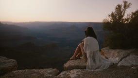 Zwolnione tempo filmowy strzał, szczęśliwa młoda kobieta z włosianym dmuchaniem w wiatrowym obsiadaniu przy breathtaking zmierzch zbiory