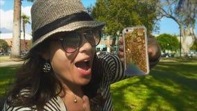 Zwolnione tempo kobieta przy parkową pokazuje telefon komórkowy pokrywą z błyskotliwością kamera zdjęcie wideo