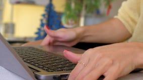 Zwolnione tempo kobieta stacza się w górę rękawa obsiadania laptopem przy stołem zdjęcie wideo