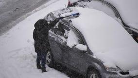 Zwolnione tempo ludzie czyści śnieg i lód z jej samochodowego wiatrowej osłony okno zdjęcie wideo