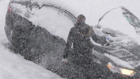 Zwolnione tempo ludzie czyści śnieg i lód z jej samochodowego wiatrowej osłony okno zbiory wideo