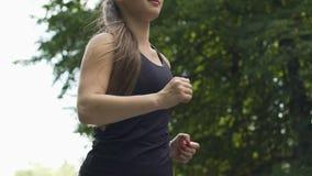 Zwolnione tempo młoda kobieta biega outdoors, długi piękny włosiany żeński jogging park zbiory