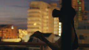 Zwolnione tempo młoda kobieta na dach rzeczywistości wirtualnej tarasowej używa słuchawki i mieć VR doświadczenie przy nocą