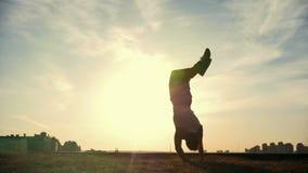 Zwolnione tempo - młoda samiec Parkour tricker bluza wykonuje zadziwiać trzepnięcia przed słońcem zbiory wideo