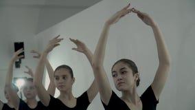 Zwolnione tempo młode baleriny które utrzymują tamte ręki nad głowa ja baletnicza pozycja zbiory
