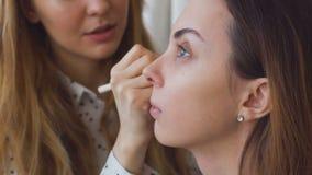Zwolnione tempo młody makijażu artysta robi dziewczynie pięknemu makeup zbliżeniu przed znacząco wydarzeniem zbiory
