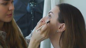 Zwolnione tempo młody makijażu artysta robi dziewczynie pięknemu makeup zbliżeniu przed znacząco wydarzeniem zdjęcie wideo