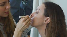 Zwolnione tempo młody makijażu artysta robi dziewczynie pięknemu makeup zbliżeniu przed znacząco wydarzeniem zbiory wideo