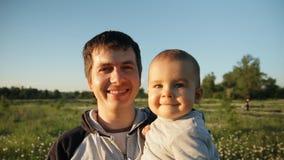 Zwolnione tempo młody szczęśliwy dziecko w kwiatu polu przy zmierzchem i ojciec zbiory wideo