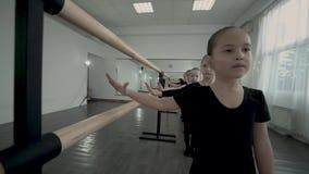 Zwolnione tempo małe baleriny jest statywowy jeden po drugim i stawia tamte ręki na baletniczym barre w tym samym czasie zdjęcie wideo