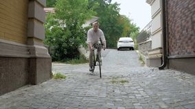 Zwolnione tempo materiał filmowy młodego brodatego mężczyzna rocznika sporta bicyklu jeździecki puszek wąska ulica z brukującą dr zdjęcie wideo