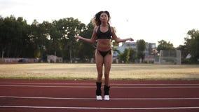 Zwolnione tempo napad, mięśniowa kobieta w czarnym bikini doskakiwaniu, używać w stadium omijający arkanę outdoors Frontowy widok zbiory wideo