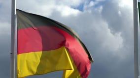 Zwolnione tempo niemiec flagi falowanie w wiatrze na flagpole przy miastem Niemcy
