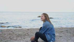 Zwolnione tempo piękna dziewczyna odpoczywa, siedzi morzem i pozuje na, kamerze na tle morze i niebie na ciepłym lecie zbiory