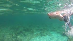 Zwolnione tempo piękna młoda kobieta w czarnym bikini brać pływać podwodny w błękitne wody z maską i snorkel na im zbiory