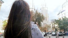 Zwolnione tempo piękna młoda kobieta z długie włosy robi fotografiami ulica przy wietrznym dniem zbiory wideo