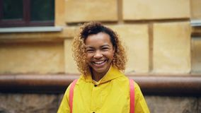 Zwolnione tempo portret śliczna mieszana biegowa dziewczyna patrzeje kamerę i uśmiechniętego trwanie outside w z kędzierzawym wło zbiory wideo