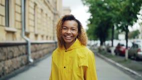 Zwolnione tempo portret amerykanina afrykańskiego pochodzenia nastolatka odprowadzenie w ulicie, kręcenie kamera i patrzeć kamerę zdjęcie wideo
