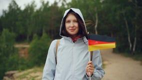 Zwolnione tempo portret atrakcyjna Niemiecka kobiety mienia flaga Niemcy, uśmiechnięty i patrzejący kamerę patriotyzm zbiory