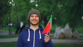 Zwolnione tempo portret atrakcyjnego mężczyzna sportowa falowania Portugalska flaga Portugalia, uśmiechnięty i patrzejący kamerę zdjęcie wideo