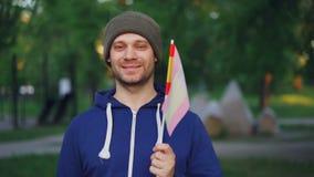 Zwolnione tempo portret brodate młodego człowieka falowania hiszpańszczyzny zaznacza i patrzejący kamerę z szczęśliwą uśmiech poz zdjęcie wideo