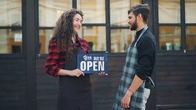 Zwolnione tempo portret dwa szczęśliwych przedsiębiorców cukiernianego właściciela pozuje z otwartym znakiem przed nowym budynkie zdjęcie wideo