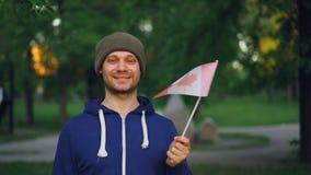 Zwolnione tempo portret Kanadyjska sporta fan falowania urzędnika flaga Kanada z szczęśliwym uśmiechem i patrzeć kamerę zbiory wideo