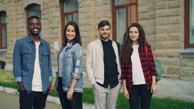 Zwolnione tempo portret piękni młodzi ludzie mężczyzna i kobiety stoi outdoors w uliczny uśmiechniętym i patrzeje zbiory wideo