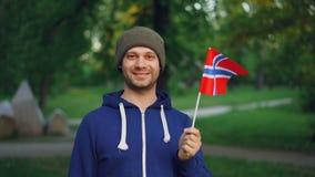 Zwolnione tempo portret przystojna Norweska sporta fan falowania flaga państowowa Norwegia pozycja w parkowym i uśmiechniętym zbiory wideo