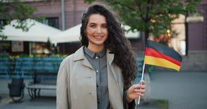 Zwolnione tempo portret stoi outdoors z flagą Niemcy Niemiecki patriota zbiory