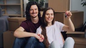 Zwolnione tempo portret szczęśliwy pary mienie wpisuje w nowym płaskim obsiadaniu na podłodze zbiory wideo